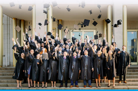Absolventen der HHL werfen zur Feier ihres Abschlusses ihren Doktorhut gemeinsam in die Höhe.