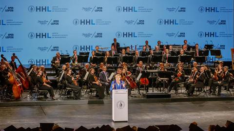 Dr. Angela Merkel hält eine Rede in der Oper Leipzig. Im Hintergrund ist das Gewandhausorchester zu sehen.