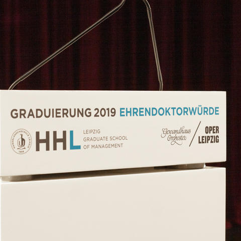 Das Rednerpult in Nahaufnahme zeigt das Logo der HHL, sowie des Gewandhausorchesters und der Oper Leipzig.