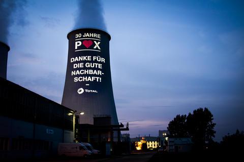 Auf einen Kühlturm der Total Raffinerie Mitteldeutschland GmbH wird eine Pani-Projektion geworfen, um für die gute Beziehung zur Nachbargemeinde zu danken.