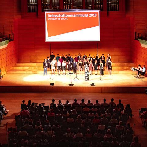 Auf der großen Bühne der Händelhalle in Halle (Saale) moderiert Laura Hempel. Der Bürgerchor Hohe Vier e.V. sorgt für musikalische Untermalung.